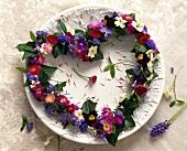 Heart-shaped flower wreath on white plate