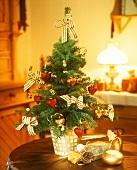 Kleiner Weihnachtsbaum und Geschenksäckchen auf einem Tisch