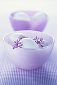 Two purple bowls with white eggs and lilac
