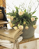 Still life with folded washing and bouquet of tulips