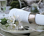 Place setting with white napkin and apple blossom