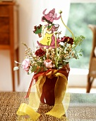 Flower arrangement in shades of red with wooden figure