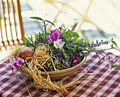 Terracotta bowl of summer flowers decorated with raffia