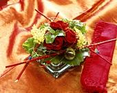 Kleines Rosengesteck eingerahmt von roten Stäben