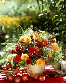 Autumn table decoration with bouquet of dahlias & small apples