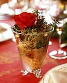 Glass decorated for Christmas with rose, fir and angel's hair
