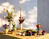 Table with various spring flowers in pots and vases