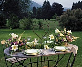 Laid table with arrangements of lilies, astilbe, Ageratum
