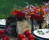 Flower arrangement in vibrant colours surrounded by tomatoes