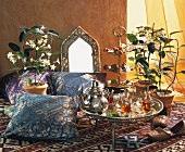 Tray of Middle Eastern tea glasses, cushions & Stephanotis