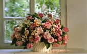 Bouquet of pink roses in front of window
