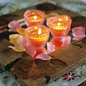 Three candles and rose petals on a table