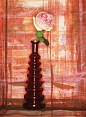 A rose in a red glass vase