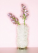 Two pink lilac flowers in a pearly vase