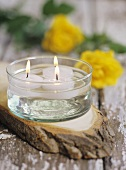 Three floating candles on a wooden platter