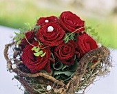 A bouquet of roses with beads surrounded by a wreath of twigs