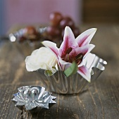 A lily and a white rose in a small silver bowl