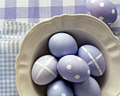 Six purple Easter eggs on a plate