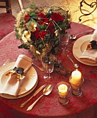Christmas arrangement of roses, two place-settings beside it