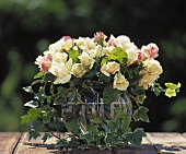 White and pastel-coloured roses with ivy in bulbous glass vase
