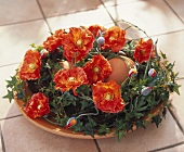 Brown eggs in terracotta bowl with artificial poppies and ivy