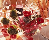 Small glass of moss and glass bowl of red anemones