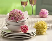 Balls of flowers and crockery on table