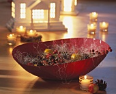 Bowl of berries, fir cones, apples, sisal and tea lights