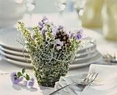 Winter arrangement of white heather, fir cones & bluebells