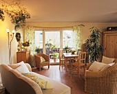 Comfortable country-house interior with houseplants amongst wood & rattan furniture
