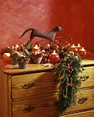 Advent decoration: round candles, mini-rocking horse & juniper
