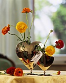 Yellow, red & orange ranunculuses in a heart-shaped vase