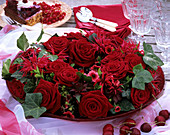 Romantic table decoration of red roses, Monarda & ivy on plate
