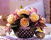 'Geisha' rose and poinsettia in metal basket