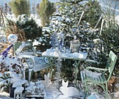 Garden furniture and fir tree, covered in snow