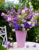 Campanulas, catmint and grasses in pink vase
