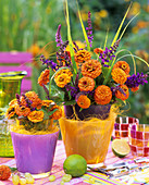 Orange zinnias, grasses and sage in glass with sisal