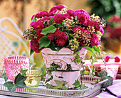 Chrysanthemums, ivy and seed heads in pink pot