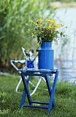 Flowers in a blue milk can on a stool