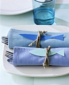 Two sets of cutlery wrapped in napkins
