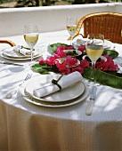 Gedeckter Tisch mit Tapas auf Bananenblättern & Blüten