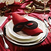 Festive table setting with red napkin & black mask