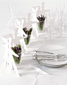 Paper figures and flowers in glasses on wedding table