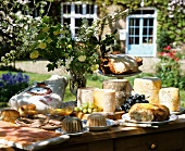 A buffet with old French cheese and ham in a summer garden