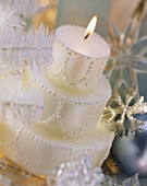 White candle in shape of three-tiered Christmas cake