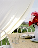 Table in open air with glasses, plates and peonies