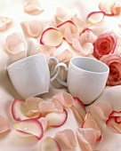 Cups with handles entwined, with rose petals