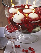 Table decoration: bowl of white floating candles and rose hips