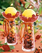 Yellow candles on glasses filled with rose hips & chestnuts
