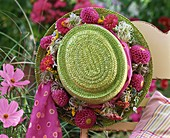 Green straw hat with wreath of dahlias on garden chair